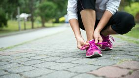 Jogger tighten her running shoe laces Stock Image