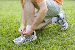 Jogger tying his shoes. Jogger or runner tying his shoes in green grass Royalty Free Stock Photography