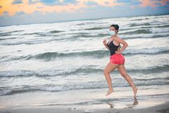 Jogger woman on beach during vacation Covid