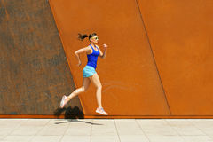 Jogger woman jump by the wall in city. Stock Photo