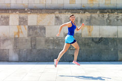 Jogger woman jump by the wall in city. Royalty Free Stock Photos