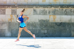 Jogger woman jump by the wall in city. look behind. Royalty Free Stock Photo
