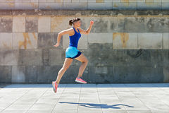 Jogger woman jump by the wall in city. Royalty Free Stock Photography