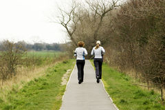 Joggers. Two female joggers running along pathway Royalty Free Stock Photos