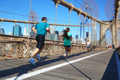Joggers on Brooklyn bridge in New York. Joggers run on the footpath of Brooklyn Bridge, that connects the boroughs of Manhattan and Brooklyn by spanning the East stock images