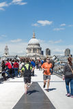 Joggers on London's Millennium Bridge. LONDON, UK - MAY 13, 2015: Joggers run on the Millennium bridge with St Pauls in the background on a sunny summer day Royalty Free Stock Image