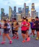 Joggers na iluminującym Singapur deptaku obraz royalty free