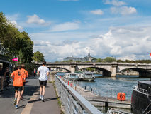 Joggers run on Berges de Seine with Seine river and Grand Palais Royalty Free Stock Photography