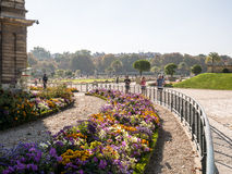 Joggers run beside curved railing along decorative flower beds o Royalty Free Stock Image