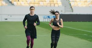 Joggers Running on Stadium. Couple of joggers running on stadium dressed in fitness outfit and glasses, workout before marathon stock footage