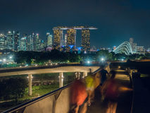 Joggers at Singapore`s Marina Barrage with city skyline. Joggers running at the Marina Barrage with Gardens by the Bay, the Conservatories and Marina Bay Sands Stock Photo