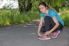 Joggervrouw die in openlucht haar schoenen binden Stock Fotografie