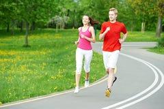 jogging νεολαίες γυναικών ανδρών υπαίθρια Στοκ Φωτογραφίες