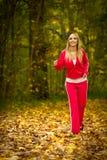 Jogging белокурой молодой женщины девушки бежать в падении Forest Park осени Стоковые Фотографии RF
