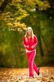 Jogging белокурой молодой женщины девушки бежать в падении Forest Park осени Стоковая Фотография