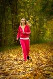 Jogging белокурой молодой женщины девушки бежать в падении Forest Park осени Стоковое фото RF