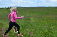 Jogging женщина и собака на поле весны Стоковая Фотография RF