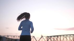 jogging заход солнца резвит девушка jogging вдоль портового района приниманнсяый за спортсмен резвится outdoors