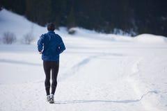 Jogging на снеге в лесе Стоковое Изображение RF