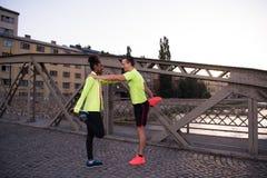 Jogging пары нагревая и протягивая в городе Стоковая Фотография RF