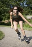 Jogging. Model Release 350 Young woman in early 20s roller blading in park stock photo