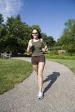 Jogging. Model Release 350 Young woman in early 20s walking in park royalty free stock photo