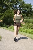 Jogging. Model Release 350  Young woman in early 20s walking in park Royalty Free Stock Images