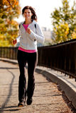 Jogging. A young woman jogging on a path in a park royalty free stock photography