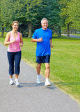 Jogging. Happy elderly seniors couple jogging in park Stock Photography