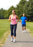 Jogging. Happy elderly seniors couple jogging in park stock image