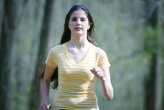 Jogging. Young woman jogging in forest royalty free stock image