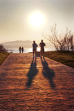 Jogging. Silhouette of people jogging and walking in Getxo park at sunset royalty free stock photo
