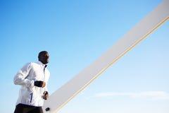 Подходящий темнокожий человек jogging быстро на заходе солнца Стоковое Изображение RF