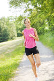 Jogging. Young blond woman jogging on pathway in park stock photography