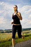 Jogging. A woman jogging cross country stock image