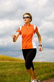 Jogging. A woman jogging cross country royalty free stock images