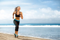 Jogging athlete woman running at sunny beach Stock Photos