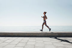 Jogging athlete young woman running at sea background Stock Photo