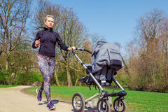 Jogging with a baby buggy Royalty Free Stock Images