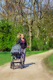 Jogging with a baby buggy. Active young woman jogging in a park with a baby buggy Royalty Free Stock Photo