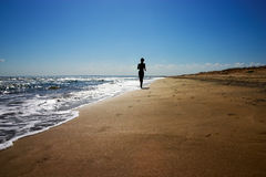 Jogging on the beach. Boy goes jogging on the beach along the waters royalty free stock images