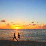 Jogging on the beach. Two people jogging on the beach at sunset forming motion silhouettes stock image