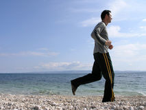 Jogging at the beach. Young man is running along the shore in a sunny day royalty free stock photos