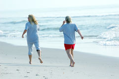 Jogging the beach. Two friends jogging at the beach Stock Images