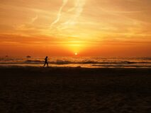Jogging on beach at sunset Stock Photography