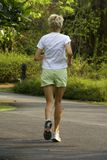 Jogging caucasian lady in park Stock Photography