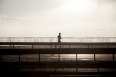 Jogging in a city. Silhouette of running man on the highway at sunrise Stock Images