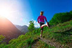 Jogging through the countryside on the mountain path Girl. Jogging through the countryside on the mountain path of a girl from behind beautiful athletic stride Stock Images