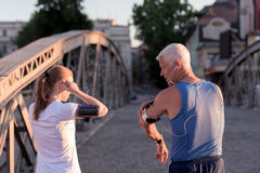 Jogging couple planning running route and setting music stock photography