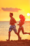 Jogging couple running exercising at sunset beach. Fitness people, men and women training outside by the ocean sea in beautiful sunset or sunrise in full body stock photography